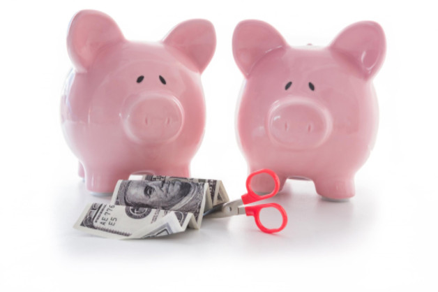 piggy banks with money and scissors for cutting costs