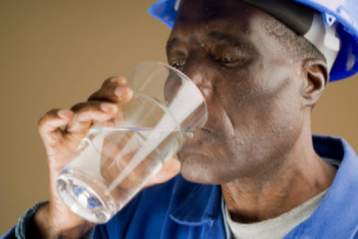 Exhausted worker drinking water: WorkingManLaw Workplace Safety Blog