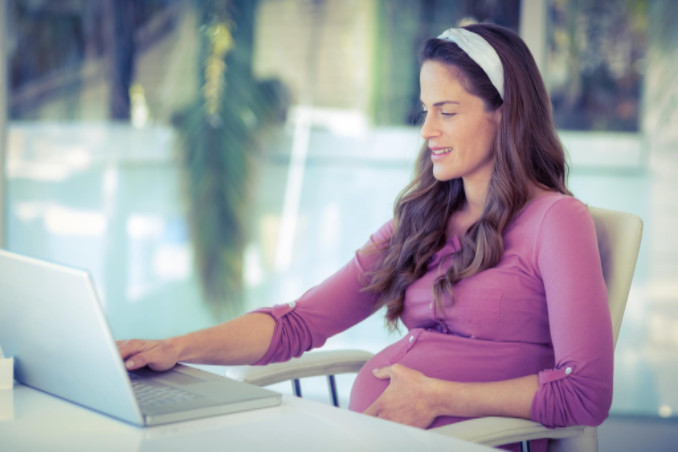 pregnant business woman working on laptop